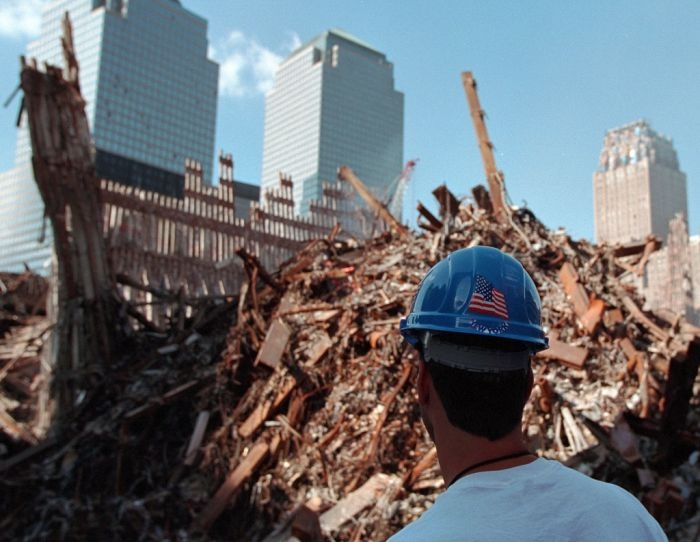 A worker stands at Ground Zero Wednesday, Oct. 3, 2001, in New York City, by Paul Morse. Public domain.