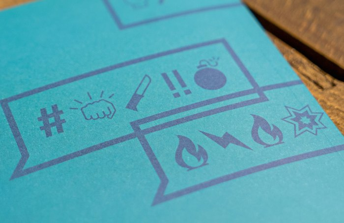 Picture: Hatespeech symbols from social media on a printed booklet by Mika Baumeister, license Unsplash